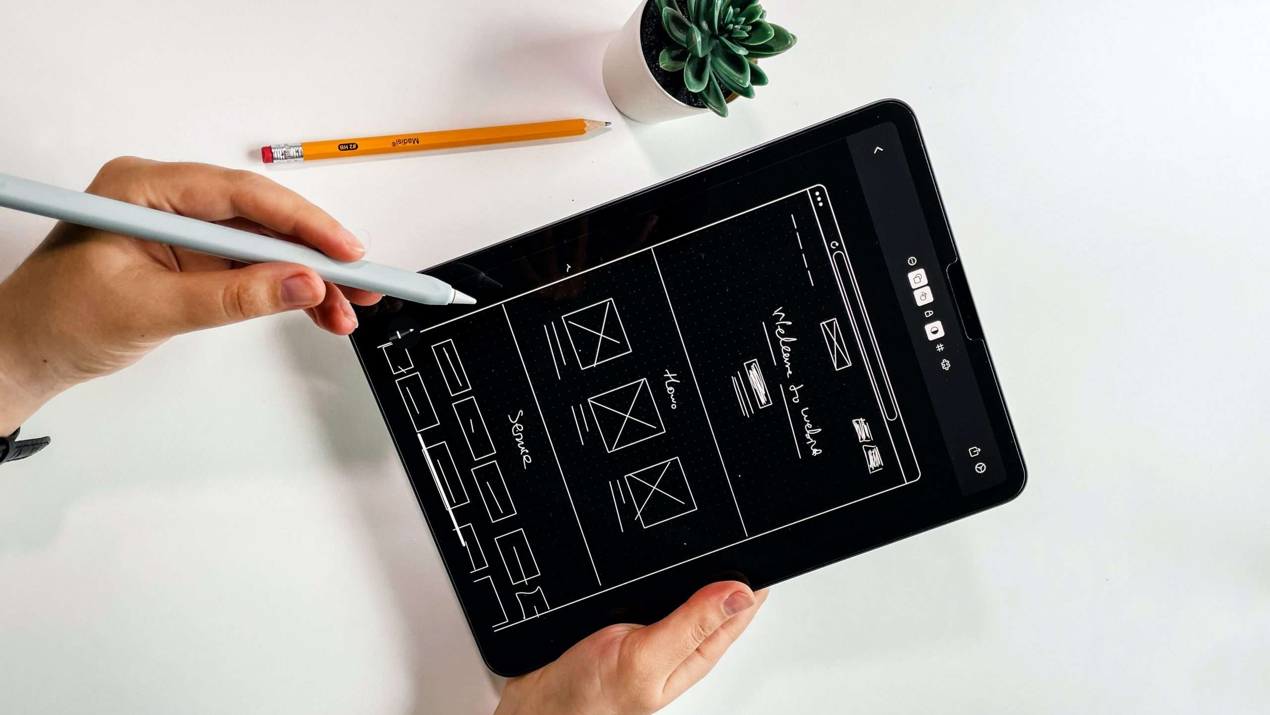 A hand is drawing wireframes in a tablet.